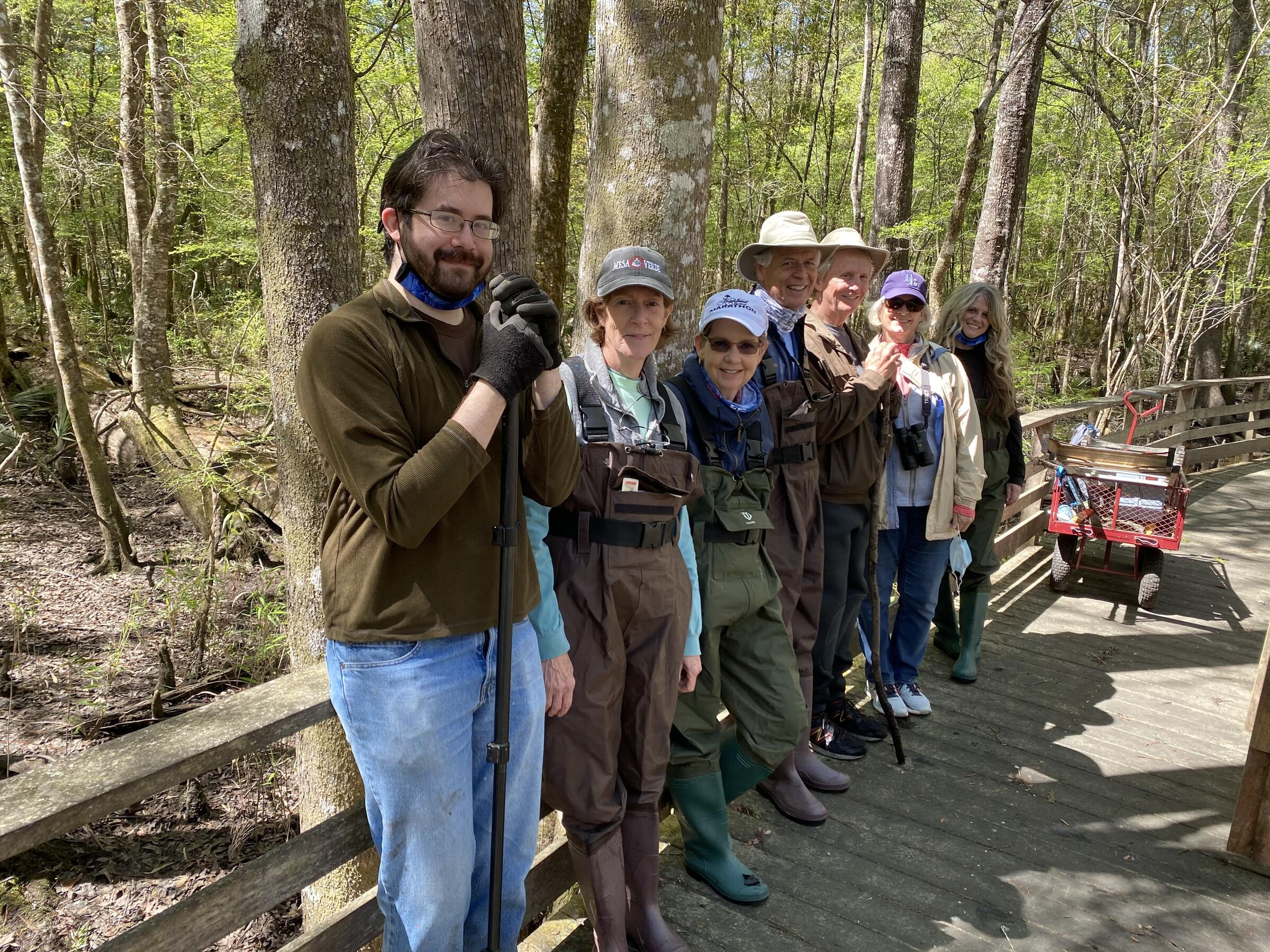 Seven people are lined up against the side of a boardwalk, some wearing waders and others wearing jeans. A red wagon with a ladder is in the distance and lush green forest behind the line of volunteers.